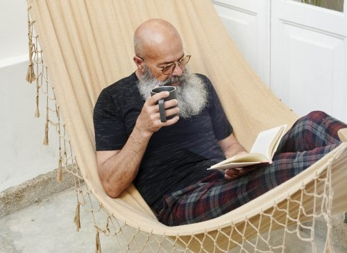 Mature man lying in a hammock on his patio reading a book and drinking a cup of coffee